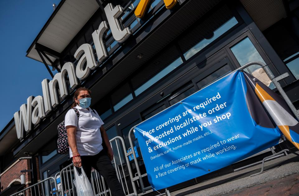 A woman wearing a facemask walks past a sign informing customers that face coverings are required in front of a Walmart store in Washington, DC on July 15, 2020. - Walmart will require shoppers to wear face masks starting next week, the US retail giant announced on July 15, joining an increasing number of businesses in mandating the protection amid the latest spike in coronavirus cases. (Photo by ANDREW CABALLERO-REYNOLDS / AFP) (Photo by ANDREW CABALLERO-REYNOLDS/AFP via Getty Images)
