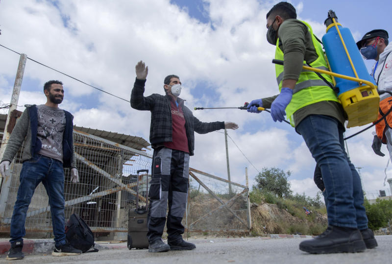 In this Tuesday, April 7, 2020 photo, a paramedic from the Palestinian Ministry of Health disinfects Palestinian laborers to help contain the coronavirus, as they exit an Israeli army checkpoint after returning from work in Israel, near the West Bank village of Nilin, west of Ramallah. The virus outbreak poses a major dilemma for tens of thousands of Palestinian laborers working inside Israel who can no longer freely travel back and forth. (AP Photo/Nasser Nasser)