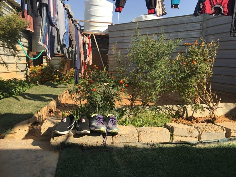 """<span class=""""caption"""">Shoes left outside to preserve the cleanliness of the inhabited interior space, with marigolds and other plants grown in the background of the man-made courtyard. Photograph taken in Zaatari Refugee Camp, 2019.</span> <span class=""""attribution""""><span class=""""license"""">Author provided</span></span>"""
