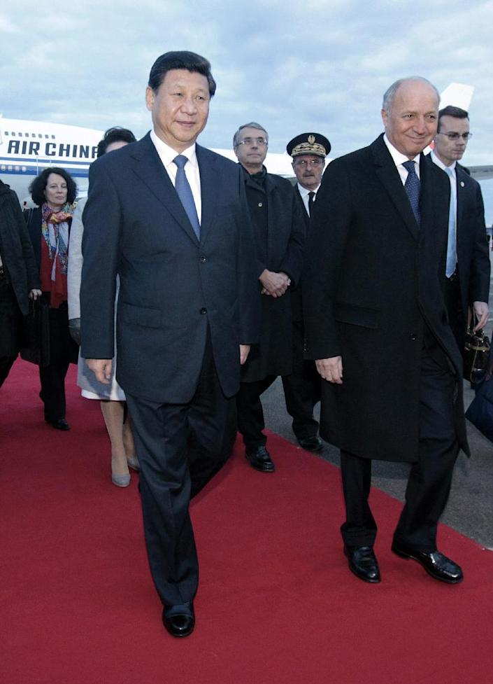Chinese President Xi Jinping' left. is welcomed by French Foreign Minister Laurent Fabius at Lyon airport, central France, Tuesday, March 25, 2014. Xi will later have a dinner at the Lyon town-hall and has arrived in France for a three-day state visit. (AP Photo/Str)