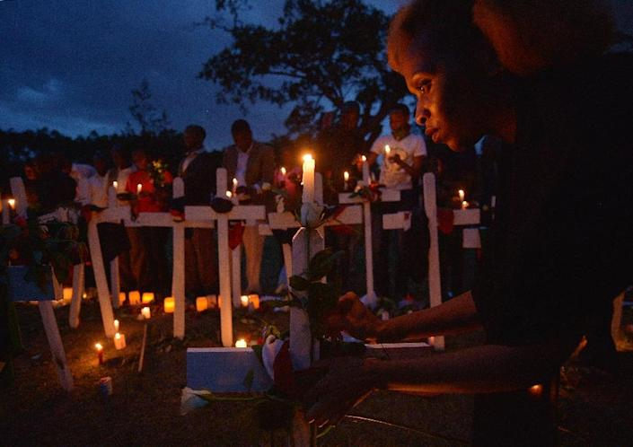 People hold candles, roses and wooden crosses in Nairobi on April 8, 2015 on the second day of a week-long candlelight vigil mourning the 148 people killed on April 2 by Somalia's Shebab Islamists (AFP Photo/Tony Karumba)