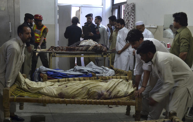 People prepare to carry the dead bodies of their relatives, victims of suicide bombing, at a hospital morgue in Mardan, Pakistan, Tuesday, June 18, 2013. A suicide bomber blew himself up in a crowd of hundreds of mourners attending a funeral in northwestern Pakistan on Tuesday, killing tens of people. Among the dead was a newly elected lawmaker who may have been the target, authorities said. (AP Photo/Mohammad Sajjad)