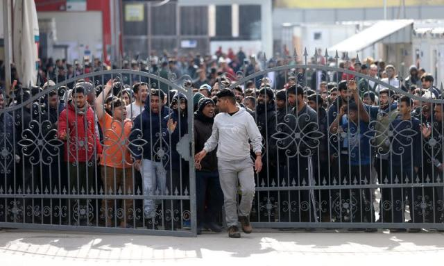 Migrants break through a fence as they protest in front of the refugee camp Miral in Velika Kladusa