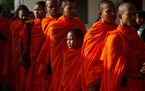 Cambodian Buddhist monks wait in queue to enter into the courtroom - Credit:  Heng Sinith/AP