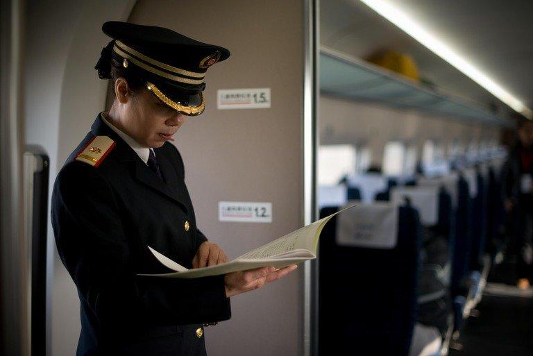 A train conductor stands aboard a high-speed train departing the Beijing West Railway Station in Beijing on December 22, 2012. China on Saturday showed off the final link of the world's longest high-speed rail route set to begin whisking passengers from the city to Guangzhou next week in a third of the time currently required