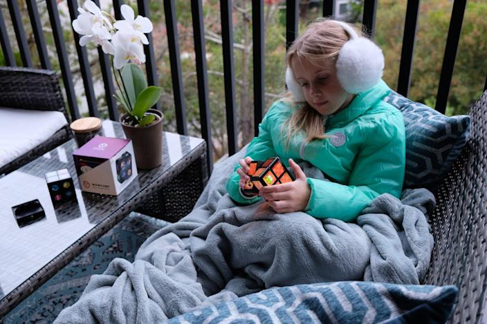 Young girl plays games on her WowCube entertainment system.