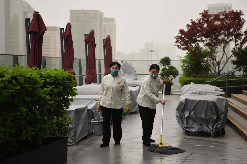 Two workers sweep the floor of an outdoor restaurant in the central business district during a sandstorm in Beijing on Thursday. Photo: AFP