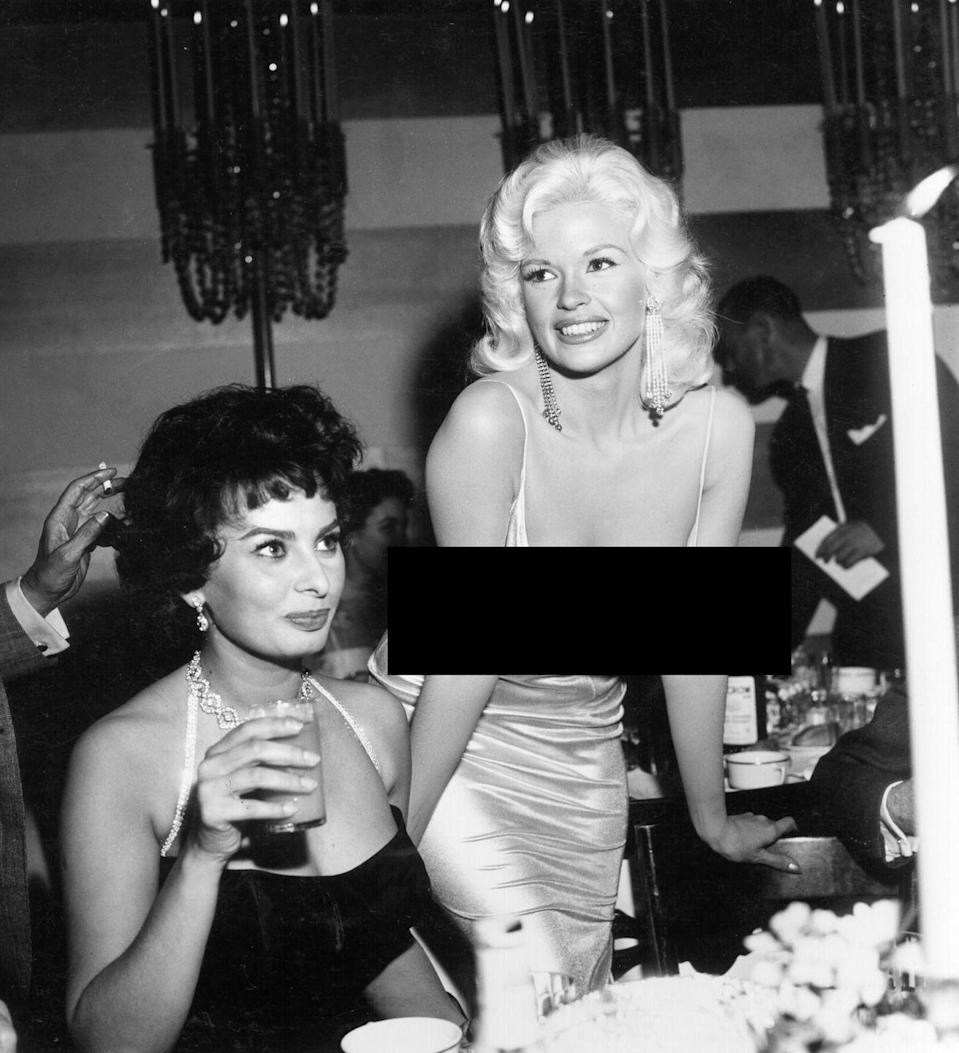 """<p>Sophia Loren was pictured <a href=""""https://www.vanityfair.com/hollywood/2014/11/story-behind-infamous-sophia-loren-jayne-mansfield-photo"""" rel=""""nofollow noopener"""" target=""""_blank"""" data-ylk=""""slk:giving some serious side-eye"""" class=""""link rapid-noclick-resp"""">giving some serious side-eye</a> to Jayne Mansfield when she entered a Paramount Studios party in 1957 wearing this low-cut dress. Loren <a href=""""https://www.vanityfair.com/hollywood/2014/11/story-behind-infamous-sophia-loren-jayne-mansfield-photo"""" rel=""""nofollow noopener"""" target=""""_blank"""" data-ylk=""""slk:said of the famous photo"""" class=""""link rapid-noclick-resp"""">said of the famous photo</a>, """"I'm staring at her nipples because I am afraid they are about to come onto my plate. In my face you can see the fear. I'm so frightened that everything in her dress is going to blow — BOOM! — and spill all over the table.""""</p>"""