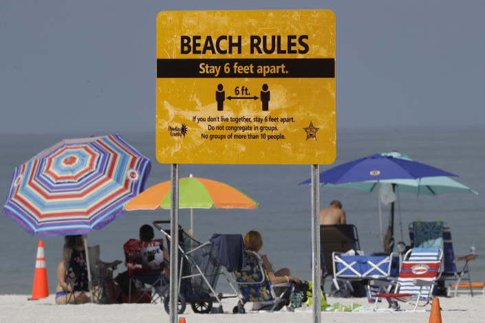 Beachgoers sunbathe near a beach rules sign after Clearwater Beach officially reopened to the public on May 4, 2020, in Clearwater Beach, Fla. (Chris O'Meara/AP)