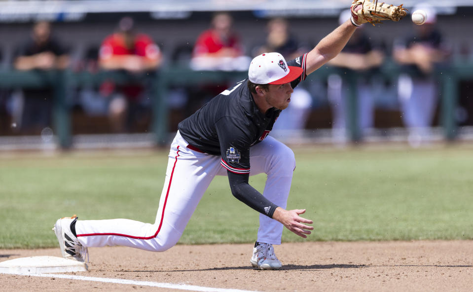 North Carolina State's Sam Highfill misses the throw to first base, allowing Vanderbilt's Dominic Keegan to reach on an error, in the fourth inning during a baseball game in the College World Series, Friday, June 25, 2021, at TD Ameritrade Park in Omaha, Neb. (AP Photo/Rebecca S. Gratz)