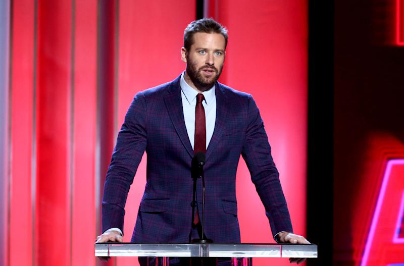 Armie Hammer looks stylish in this dark blue suit with a red tie to match