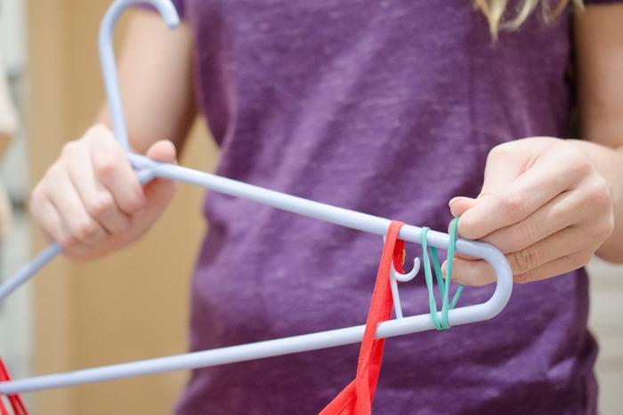 Stop clothes from slipping off hangers with a band on either side.