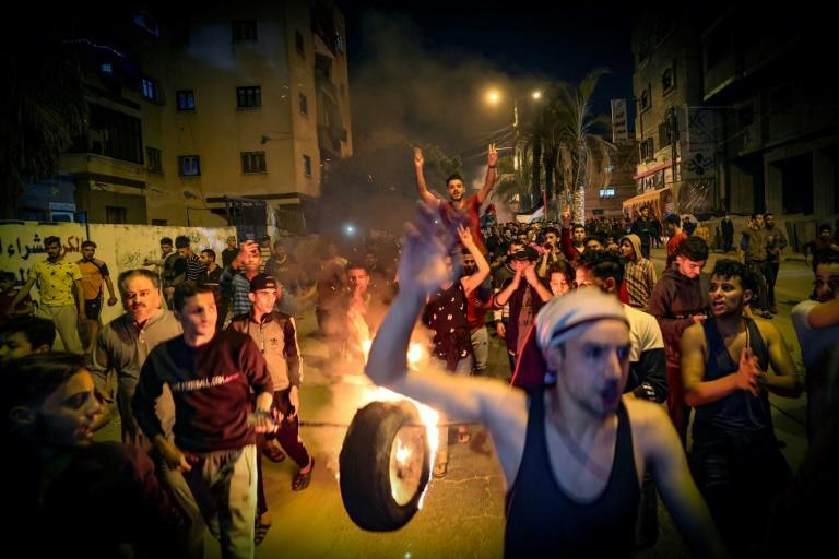 Palestinians carry a burning tyre as they shout slogans in support of the Al-Aqsa Mosque during a rally in Gaza city on April 24, 2021