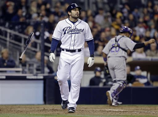 San Diego Padres' Carlos Quentin tosses away his bat as Colorado Rockies catcher Wilin Rosario heads to the dugout after Quentin struck out to end the eighth with a man on base in a tied baseball game Friday April 12, 2013 in San Diego. (AP photo/Lenny Ignelzi)