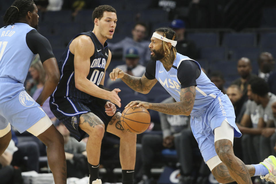 Minnesota Timberwolves' James Johnson, right, drives past Orlando Magic's Aaron Gordon in the first half of an NBA basketball game, Friday, March 6, 2020 in Minneapolis. (AP Photo/Jim Mone)