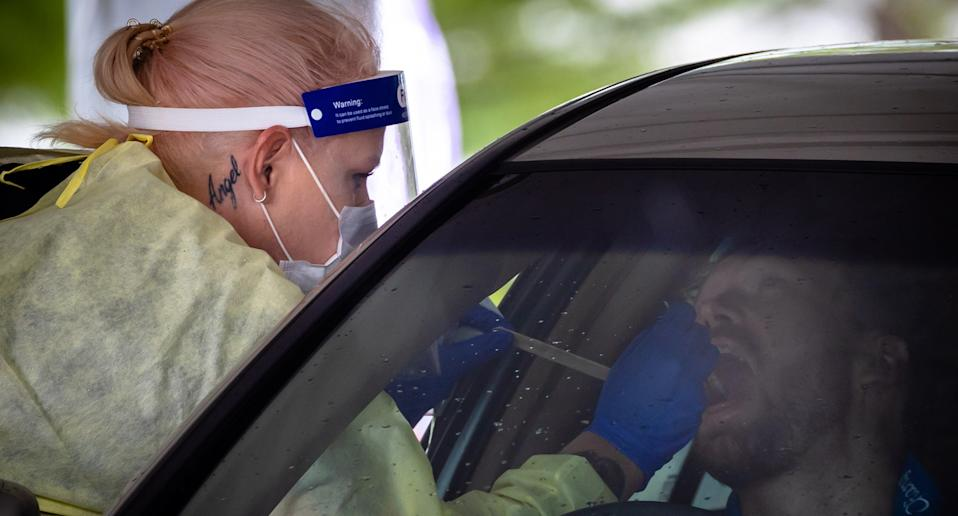 Male driver receives mouth swab from female nurse.