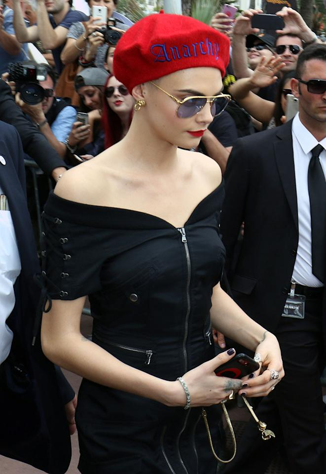 "<p>At the Cannes Film Festival in France, Cara Delevingne, who recently shaved her head for a role in a movie, wore a red beret with the word ""Anarchy"" stitched on it. She paired it with a black off-the-shoulder dress, aviator sunglasses, and matched her bright red lips to her hat. (Photo: Splash) </p>"