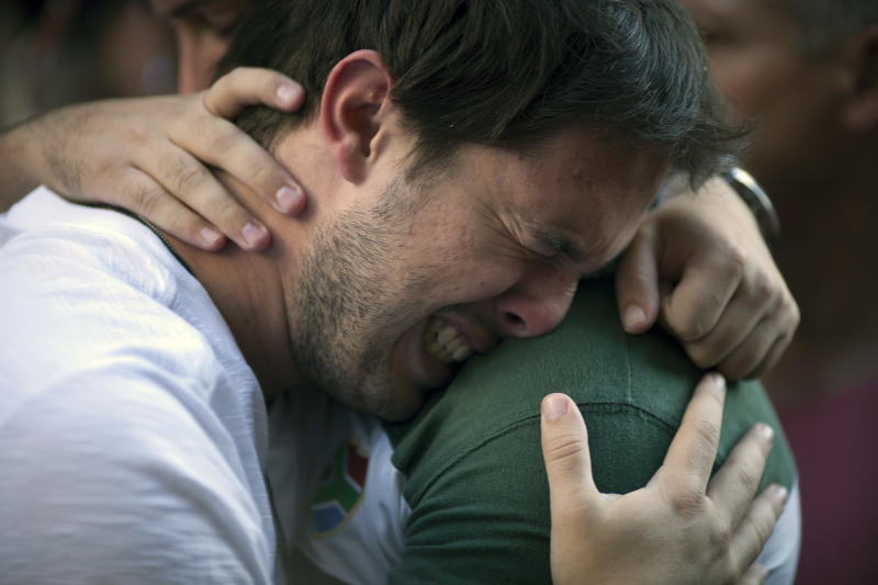A man cries during a protest near the Kiss nightclub where a fire killed over 230 people in Santa Maria, Brazil, Tuesday, Jan. 29, 2013. The blaze began at around 2:30 am local time on Sunday, during a performance by Gurizada Fandangueira, a country music band that had made the use of pyrotechnics a trademark of their shows. (AP Photo/Felipe Dana)