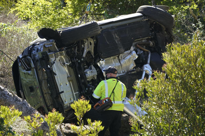 A vehicle rests on its side after a rollover accident involving golfer Tiger Woods Tuesday, Feb. 23, 2021, in Rancho Palos Verdes, Calif., a suburb of Los Angeles. Woods suffered leg injuries in the one-car accident and was undergoing surgery, authorities and his manager said. (AP Photo/Marcio Jose Sanchez)