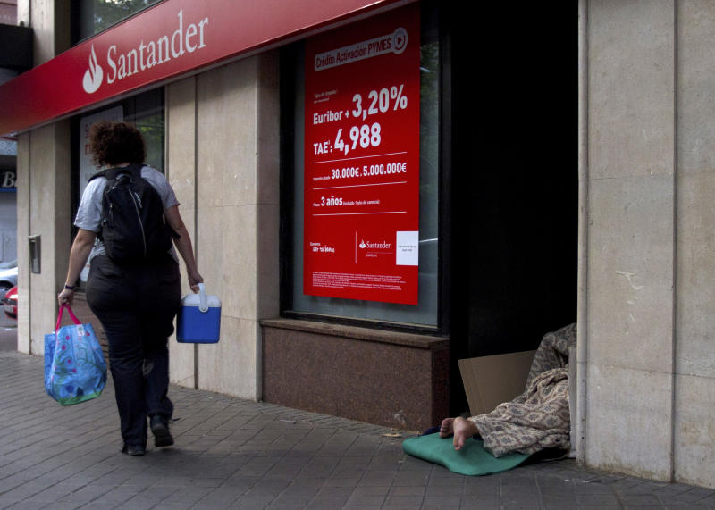 "A homeless person sleeps in the doorway of a bank in Madrid Thursday June 7, 2012. Spanish Prime Minister Mariano Rajoy pleaded with European leaders ""to support those that are in difficulty"" and push toward greater fiscal unity - a step that might allow its troubled banks to get direct financial help. The call comes although Spain insists it doesn't need outside aid. (AP Photo/Paul White)"