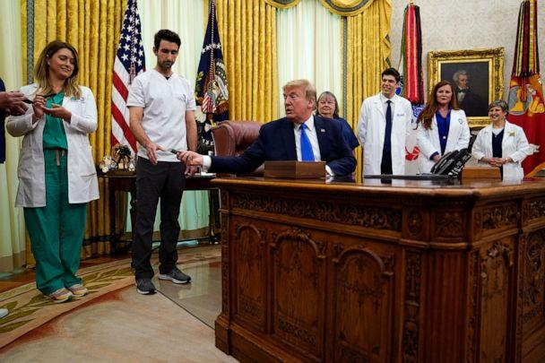 PHOTO: President Donald Trump hands a pen off after signing a proclamation in honor of World Nurses Day, in the Oval Office of the White House, May 6, 2020, in Washington. (Evan Vucci/AP)