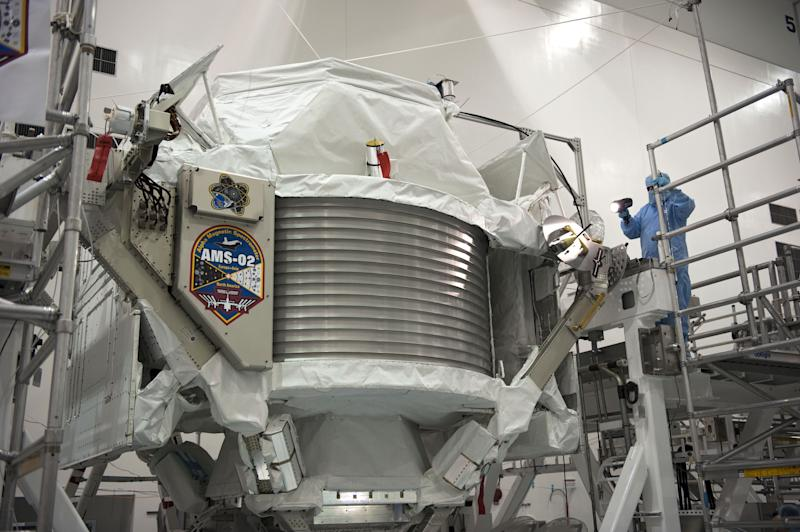 FILE -In this undated picture made available by NASA, a technician examines the Alpha Magnetic Spectrometer at Kennedy Space Center in Cape Canaveral, Fla.. The cosmic ray detector was mounted on the International Space Station, searched the universe and shall help to explain how everything came to be. CERN , the European Organization for Nuclear Research, released first results of the experiment Wednesday April 3, 2013. (AP Photo/NASA, Glenn Benson)