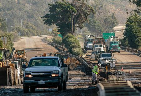 Workers on the 101 Highway clear mud and debris from the roadway after a mudslide in Montecito, California