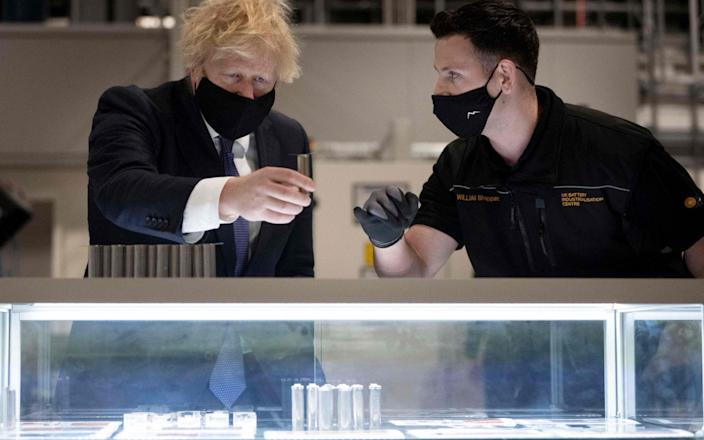Boris Johnson (L) looks at a single battery cell during a visit to the UK Battery Industrialisation Centre in Coventry - AFP