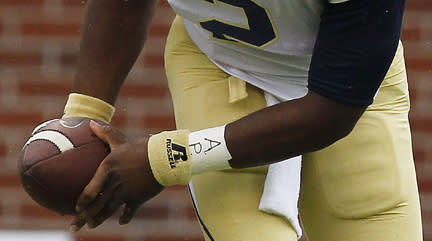 "FILE - In this Sept. 21, 2013 file photo, Georgia Tech quarterback Vad Lee (2), wears APU for ""All Players United"" on his wrist tape, as he works against North Carolina during an NCAA football game in Atlanta. The decision to allow Northwestern football players to unionize raises an array of questions for college sports. Among them, state schools vs. public schools, powerhouse programs vs. smaller colleges (AP Photo/Mike Stewart, File)"