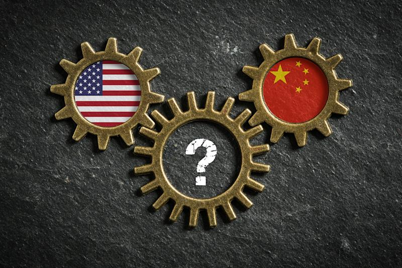 Three interlocking cogs displaying the U.S. flag, China flag, and a question mark.