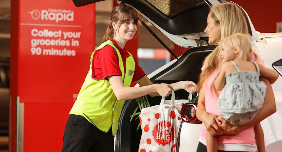 Coles employee loads a shopper's car with groceries.