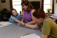 Lily Osgood, 7, who has Down syndrome, shakes hands with brother, Noah, 12, right, after solving a problem while studying with their mother, Jennifer, at their home in Fairfax, Vt., on Tuesday, July 20, 2021. The Osgood children will continued to be homeschool this upcoming school year. As the pandemic took hold across the United States in the spring of 2020, it brought disruption and anxiety to most families. Yet some parents are grateful for one consequence: they are now opting to homeschool their children even as schools plan to resume in-person classes. (AP Photo/Charles Krupa)