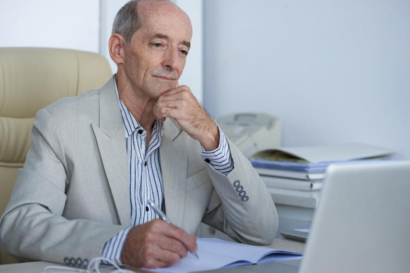 Older man in suit jotting down notes while staring at a laptop screen.