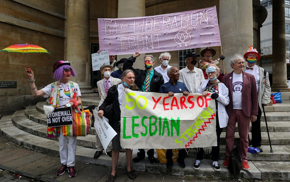 People hold placards as they take part in the Gay Liberation Front (GLF) pride march in London, Britain, June 27, 2020.