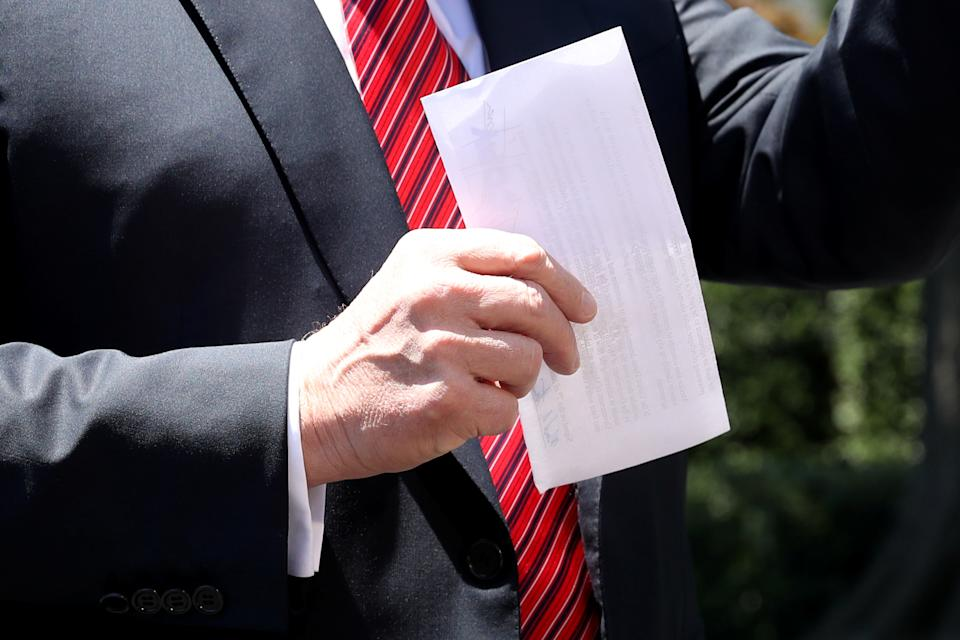 U.S. President Donald Trump holds up a copy of a deal with Mexico on immigration and trade as he speaks to the news media prior to departing for travel to Iowa from the White House in Washington, U.S., June 11, 2019. The document says the U.S.-Mexico migrant agreement reached last week includes a regional asylum plan and that Mexico agreed to examine its laws and potentially change them in order to implement the deal.  REUTERS/Leah Millis