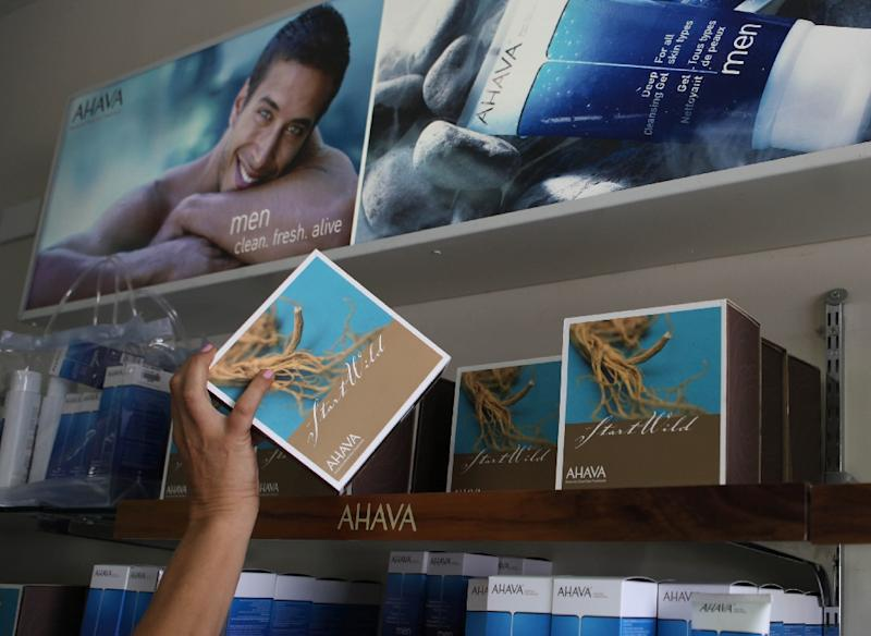 An Israeli woman reaches for an AHAVA Dead Sea cosmetic product manufactured in the Israeli Kibbutz settlement of Mitzpe Shalem, in the occupied West Bank (AFP Photo/Gali Tibbon)