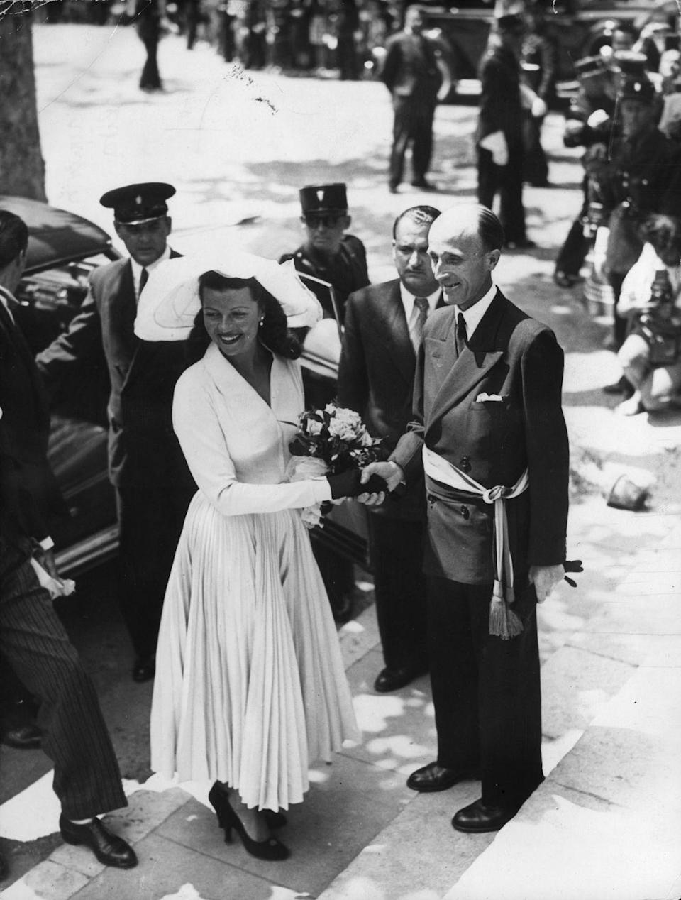 <p>Rita Hayworth arrives at her wedding to Prince Aly Khan wearing an elegant and understated dress by Jacques Fath and a wide-brimmed hat. The couple's reception was in the South of France at the Prince's Château de l'Horizon. </p>