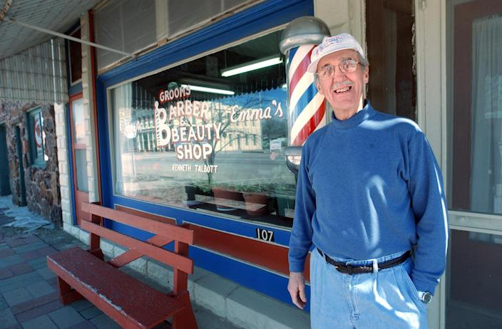 FILE - In this March 4, 2008, file photo Kenny Talbott stands next to his barber pole in front of Grooms Barber and Beauty Shop in Marquette, Kan. The barber pole, one of the oldest signs that can be seen on storefronts across America, is an increasing source of friction between barbers and beauticians over which businesses get to display the iconic striped poles. (AP Photo/The Hutchinson News, Sandra Milburn, File)