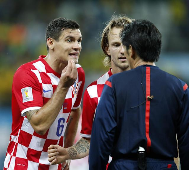 Croatia's Dejan Lovren, left, and teamamte Ivan Rakitic, center, complain to referee Yuichi Nishimura, from Japan, after Nishimura issued a penalty against Croatia during the group A World Cup soccer match between Brazil and Croatia in the opening game of the tournament at Itaquerao Stadium in Sao Paulo, Brazil, Thursday, June 12, 2014. Brazil's Neymar scored on a penalty kick following the ball helping his team to a 3-1 victory. (AP Photo/Frank Augstein)