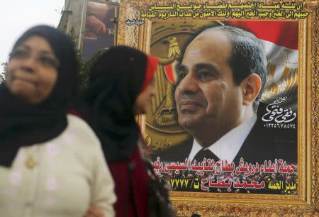 Women walk in front of huge banner for Egypt's army chief, al-Sisi in downtown Cairo
