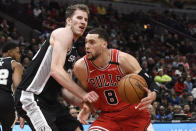 San Antonio Spurs center Jakob Poeltl (25) defends against Chicago Bulls guard Zach LaVine (8) during the first half of an NBA basketball game Monday, Jan. 27, 2020, in Chicago. (AP Photo/David Banks)
