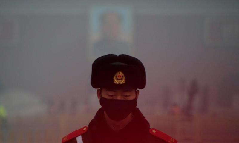 A paramilitary police officer wearing a mask stands guard in front of a portrait of the late Chairman Mao during smog at Tiananmen Square in Beijing