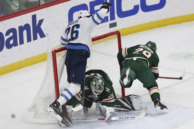 Winnipeg Jets' Blake Wheeler crashes into Minnesota Wild's goalie Devan Dubnyk after trying to score a goal in the first period of an NHL hockey game Thursday, Jan. 10, 2019, in St. Paul, Minn. (AP Photo/Stacy Bengs)