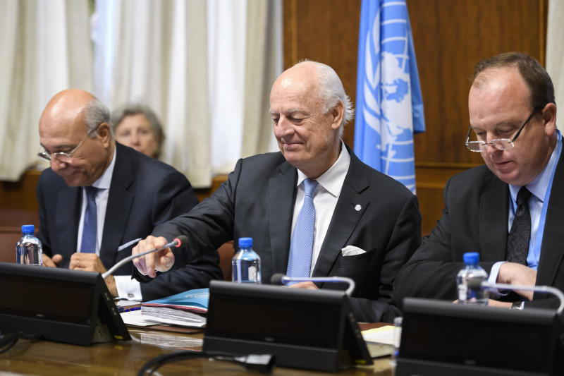 UN Special Envoy for Syria Staffan de Mistura, center, and his deputy Ramzy Ezzeldin Ramzy, left, attend a meeting with members of the Syrian government delegation during peace talks at the European headquarters of the United Nations in Geneva, Switzerland, Friday, May 19, 2017. (Fabrice Coffrini/Pool Photo via AP)