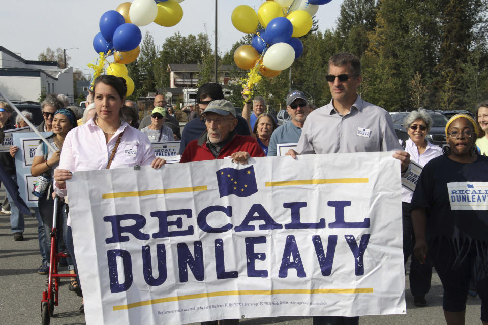 FILE - In this Sept. 5, 2019, file photo, Meda DeWitt, left, Vic Fischer, middle, and Aaron Welterlen, leaders of an effort to recall Alaska Gov. Mike Dunleavy, lead about 50 volunteers in a march to the Alaska Division of Elections office in Anchorage, Alaska. The group opposed to Dunleavy has yet to gather enough signatures to force a recall election, nearly two years after launching and with just over a year before the 2022 primary election. (AP Photo/Mark Thiessen, File)
