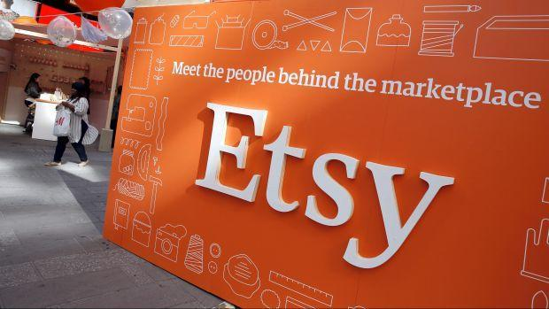 """A bright orange sign featuring the logo for online selling platform Etsy and the words """"Meet the people behind the market"""""""