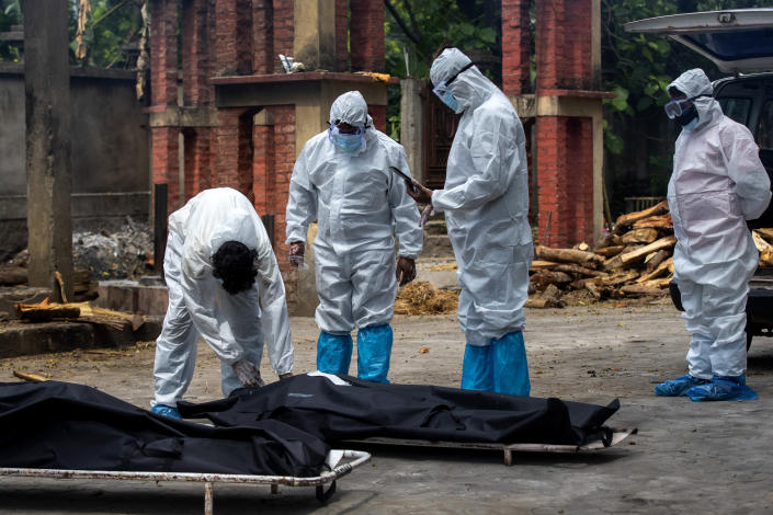 Relatives in protective suits prepare to cremate the body of a person who died of COVID-19 in Gauhati, India, Monday, May 24, 2021. India crossed another grim milestone Monday of more than 300,000 people lost to the coronavirus as a devastating surge of infections appeared to be easing in big cities but was swamping the poorer countryside. (AP Photo/Anupam Nath)