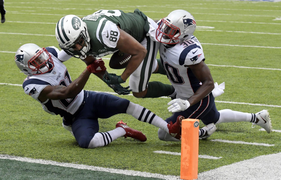 "FILE - In this Sunday, Oct. 15, 2017, file photo, New York Jets tight end Austin Seferian-Jenkins (88) loses his grip on the ball as he is tackled by New England Patriots' Malcolm Butler (21) and Duron Harmon (30) during the second half of an NFL football game, in East Rutherford, N.J. ""I just think it's too risky to do something like that,"" Jets offensive coordinator John Morton said. ""I always try to say, 'Just lower your head and finish with the ball through the end zone.' That's the best thing to do to protect it, otherwise you might fumble it through and now it's a touchback. What good does that do you? Then they have the ball and it could cost you, but it's hard. Guys are competing and they're trying to score, and it just happens. It just happens, but that's what we preach. Hold onto the ball and run into the end zone if you can with it."" The Jets were hurt by the rule earlier in the season against New England when tight end Seferian-Jenkins had the ball knocked loose just short of the end zone and recovered it while out of bounds leading to a touchback.  (AP Photo/Bill Kostroun, File)"