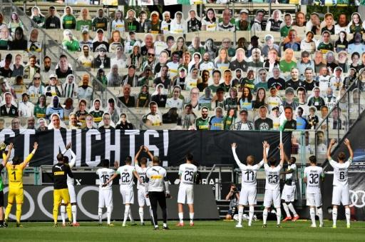 Bundesliga side Moenchengladbach celebrate in front of cardboard cutouts of fans