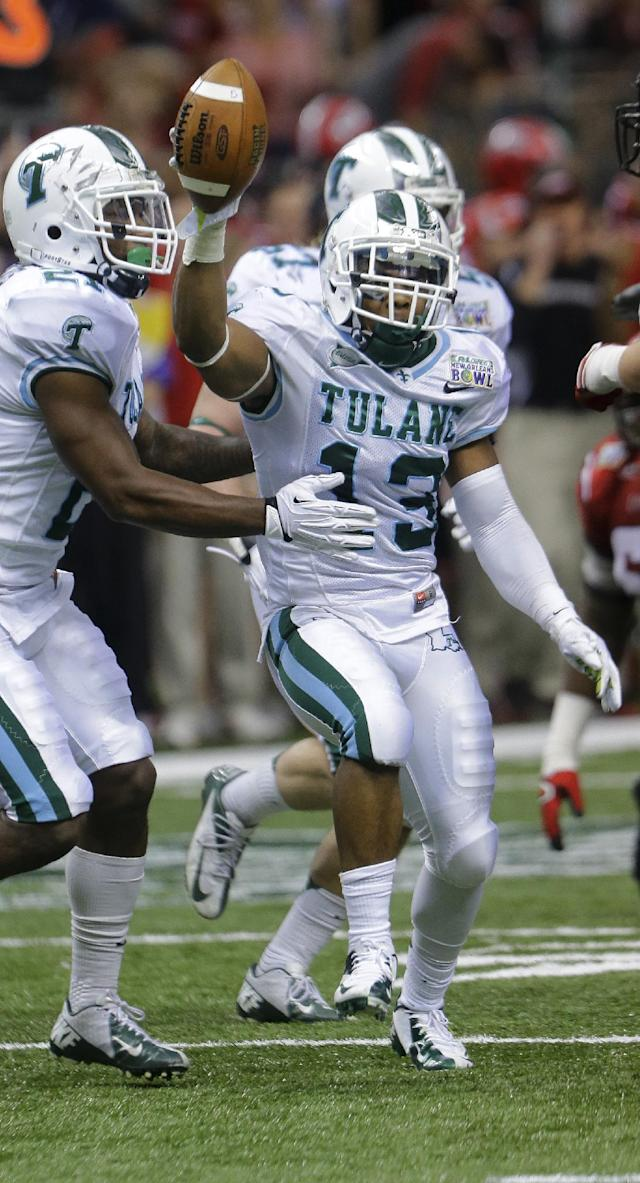Tulane cornerback Derrick Strozier (13) celebrates his interception against Louisiana-Lafayette during the second half of the New Orleans Bowl NCAA college football game in New Orleans, Saturday, Dec. 21, 2013. (AP Photo/Bill Haber)